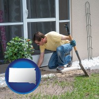 south-dakota map icon and a landscape contractor working on a landscaping project