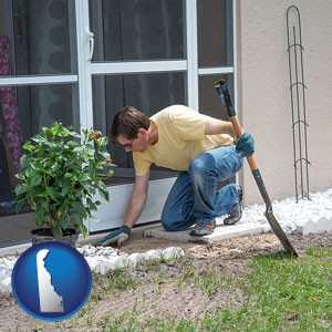 a landscape contractor working on a landscaping project - with Delaware icon